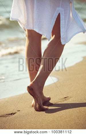 barefoot woman walk down sand beach by the sea in white long shirt, lower body, selective focus