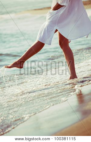 barefoot woman enjoy in sea water in white long shirt, lower body, selective focus, side view