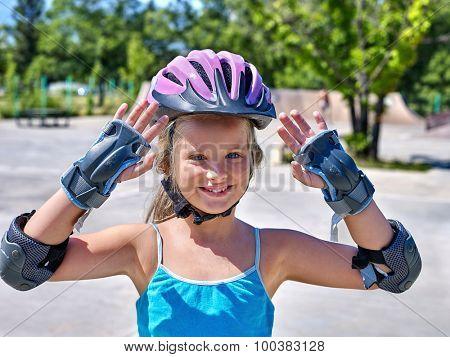 Portrait of girl in sport helmet riding on roller skates in skatepark.