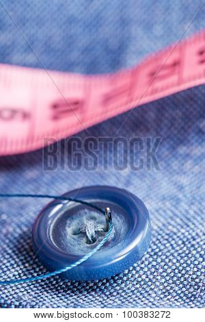 Attaching Of Button To Blue Material By Needle