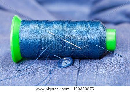 Thread Bobbin With Needle, Button On Blue Jacket