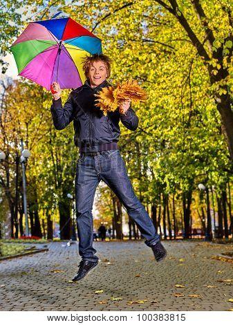 Happy man holding  autumn umbrella walking outdoor .