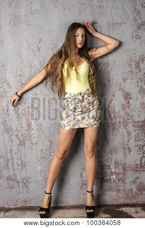 Young  girl with long hair in a tank top and mini skirt