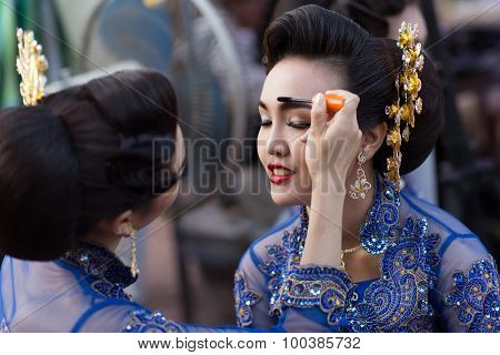 BANGKOK, THAILAND, February 17, 2015: A Thai lady traditional dancer is applying make up on eyebrow's friend before the show celebrating the new Krung Kasem floating market in Bangkok, Thailand