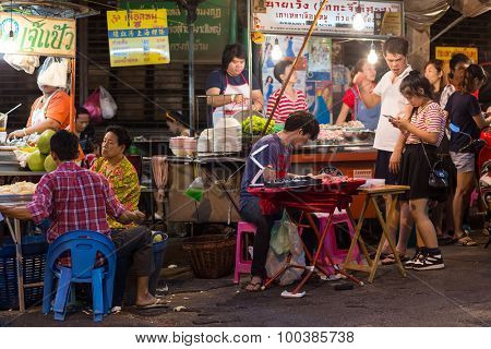 BANGKOK, THAILAND, February 18, 2015 : Some customers are sitting at the restaurant tables in a street of Chinatown in Bangkok, Thailand