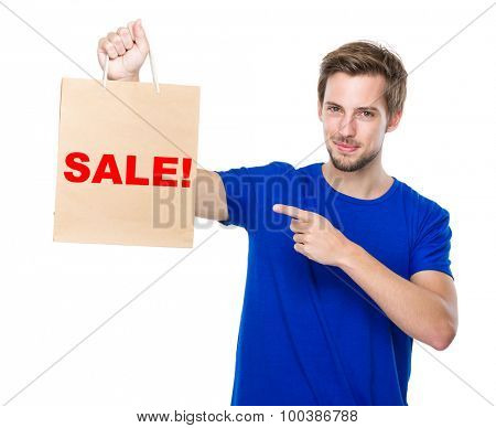 Man finger point to the shopping bag and showing a word sale!