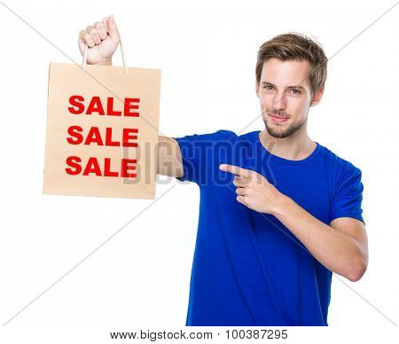 Man finger point to the shopping bag and showing three words of sale