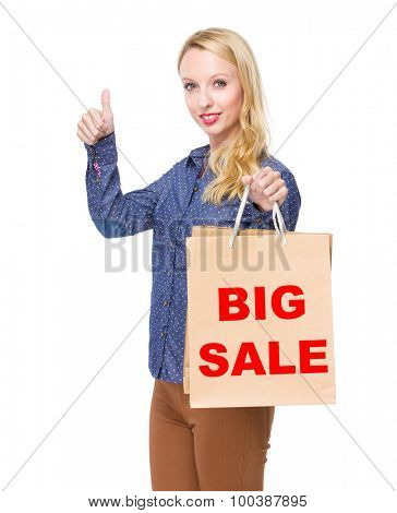 Woman with shopping bag and thumb up for showing big sale