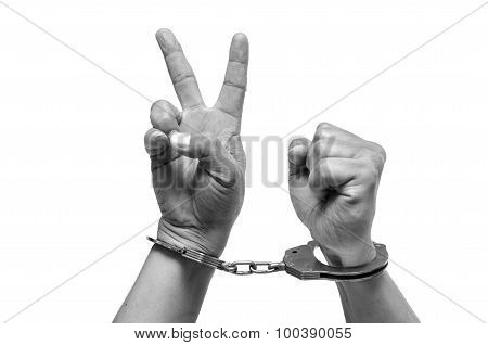 Man hands with handcuffs showing victory sign isolated on white background