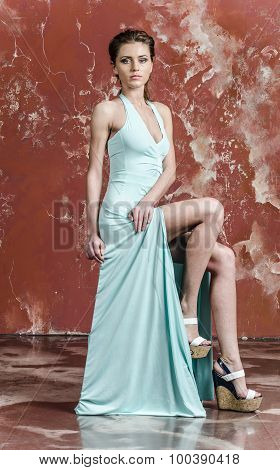 Young beautiful brown-haired woman in blue light silk dress with open shoulders and a long skirt and