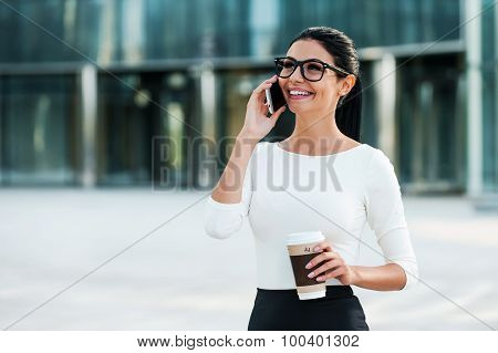 Cheerful young businesswoman talking on the mobile phone