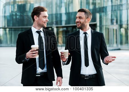 Cheerful businessmen holding cups on coffee