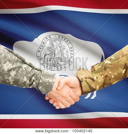 Military Handshake And Us State Flag - Wyoming