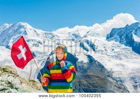 Cute little girl wearing bright rainbow colored coat, holding swiss flag