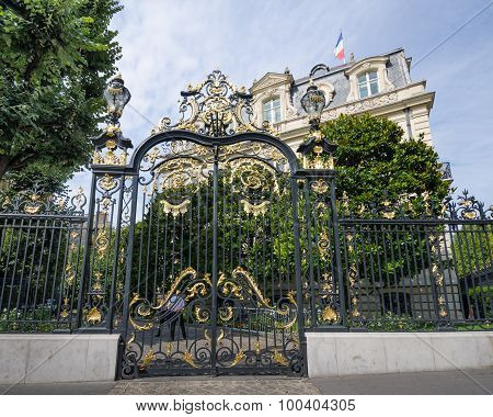 The sun glistens on the gold of an ornate gate in Paris