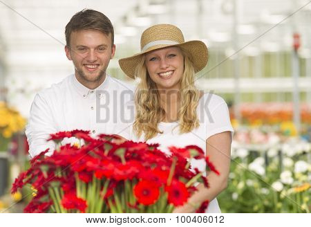 Young man and woman in a greenhouse full of flowers