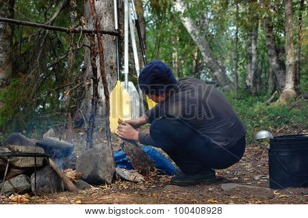 Boy lighting a camp fire.