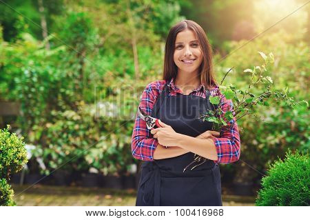 Happy Young Woman Pruning Plants In A Nursery