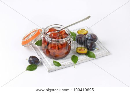 fresh and preserved plums on wooden cutting board