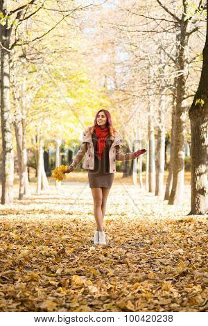 Attractive young woman walking in the park in the autumn time holding colorful foliage,