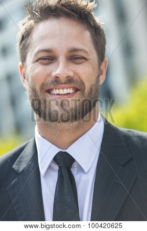 A young successful man, male executive businessman with beard smiling in front of a high rise office block in a modern city