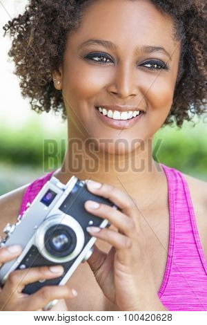 A beautiful mixed race African American girl or young woman looking happy taking pictures or photographs with a retro digital camera
