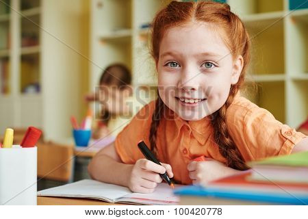 Cute pupil drawing with highlighter and looking at camera