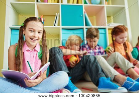 Cute schoolgirl with exercise-book looking at camera with classmates on background