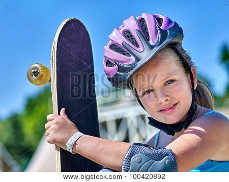 Portrait of kid with his skateboard  outdoor. Skateboard girl style.