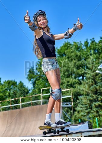 Teen girl rides his skateboard outdoor. Girl thumb up  aganist blue sky.