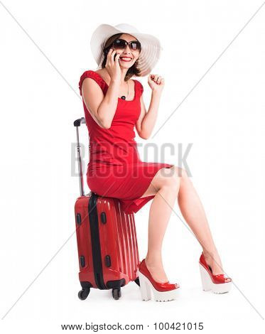 girl sitting on a suitcase and talking on a phone