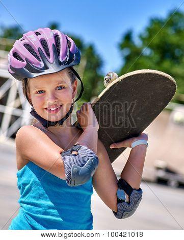Kid skateboarding his skateboard and hold on her back outdoor. Skateboard girl style.
