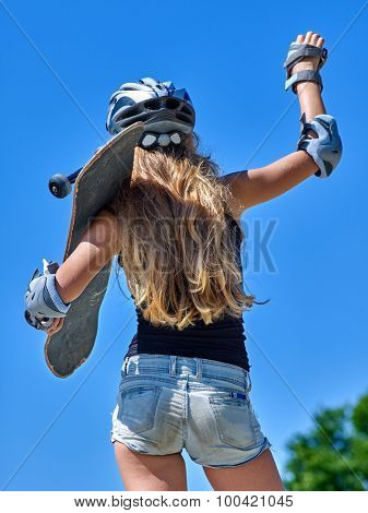 Portrait of teen girl holding his skateboard blue sky outdoor. View from the back.