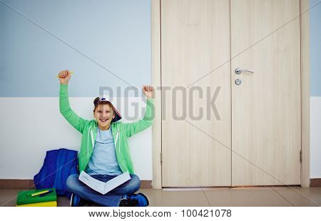 Successful schoolboy with open book and raised arms sitting by classroom door