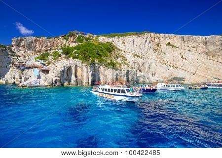 ZAKYNTHOS, GREECE - AUG 24, 2015: Boats with tourists at the Blue caves of Zakynthos island, Greece. Sunrays reflect through blue sea water from white limestones creating visual lighting effects.[