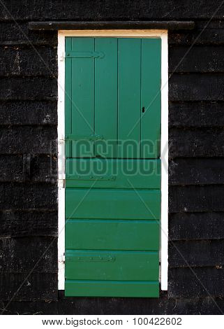 Old green wooden door with white frame and black wooden tiles