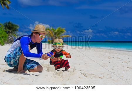 father and son playing with water guns on beach