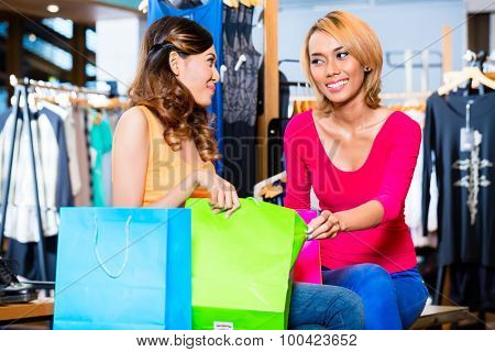 Asian girl friend fashion shopping in store showing each other their purchase in bag