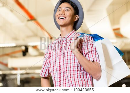 Asian young man shopping fashion in store being visibly happy