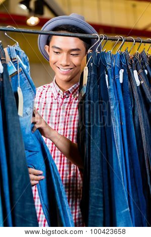 Asian man browsing jeans hanging on a clothes rack in fashion store