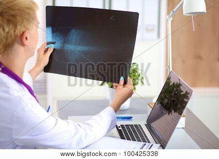Confident female doctor examining accurately a rib cage x-ray