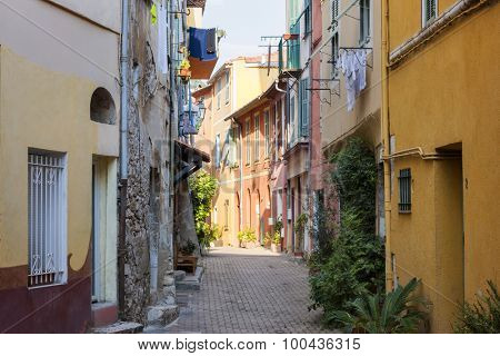 Sunny narrow street with colorful old buildings and green potted plants in medieval town Villefranche-sur-Mer on French Riviera, France.