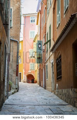 Narrow cobblestone street with bright buildings in medieval town Villefranche-sur-Mer on French Riviera, France.