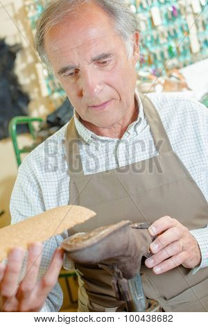 Experienced cobbler gluing a sole in place