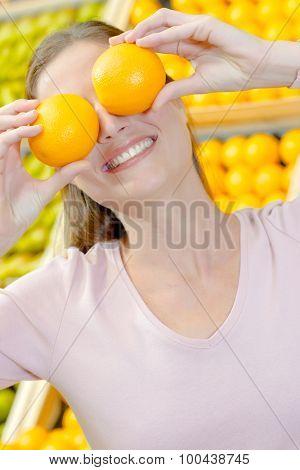 lady holding oranges over eyes