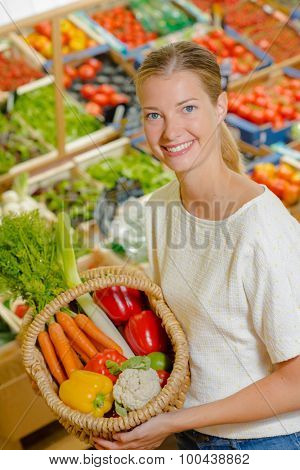 Woman holding up a basket of vegetables