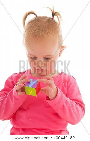 Portrait toddler girl playing with blocks isolated over white background