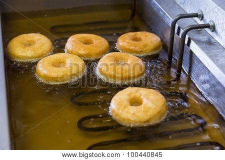 Fried Equal Round Doughnuts In Deep-fryer