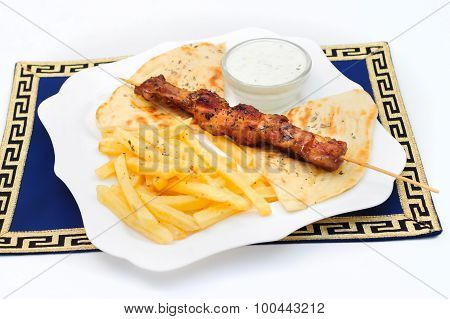 Souvlaki or kebab, grilled meat on pita bread with sauce and french fries, white plate.