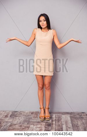 Full length portrait of a young attractive woman shrugging shoulders on gray background